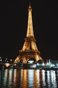 A photo of the Eiffel Tower at night, with its lights reflected in the Seine.